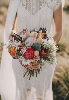 Mix up your bouquet with some gorgeous jewel tones like the magenta and orange notes in this arrangement.     Image via  Mountain Modern Life.
