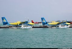 A typical scene from sea plane terminal A with the constant comings and goings of Twin Otters. Here, 8Q-TMI and 8Q-TMW are prepared for their next flights while 8Q-OEO waits for clearance for take-off as 8Q-TMV climbs out in the distance.  Trans Maldivian Airways - TMA De Havilland Canada DHC-6-310 Twin Otter 	 Male - International (MLE / VRMM) Maldives, March 9, 2014