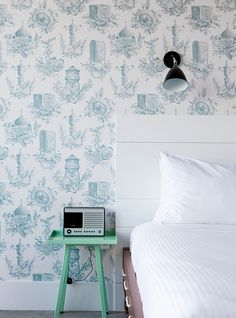 New York guidebook by Cereal magazine patterned wallpaper green bedside table bedroom white sheets