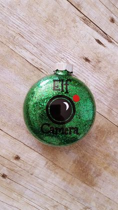 Keep your kids behaving this Christmas season with a special Elf Camera watching them and reporting back to Santa! Made of glass and approximately 4 in diameter, this disc shaped ornament has glitter on the inside (no mess!) and vinyl decorations on the outside. Can be personalized with names on the back at no extra charge.  **Please note this is NOT a real camera.