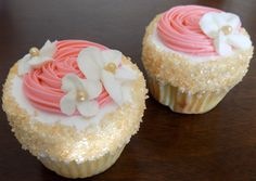 Yellow cupcakes, filled and iced with vanilla buttercream and decorated with coral rosettes and blossom flowers with gold centers