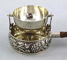 "T3388 Tea Strainer with Ornate Cup and Wood handle    A German Sterling silver swivel tea strainer on a chased sterling cup with a wooden handle. Manufactured by Berthold Muller with London import marks for 1911. Length with handle: 5 1/2""    Price: $325.00"