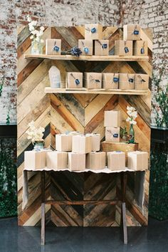 reclaimed wood wall as backdrop for jewelry display-- wrap boxes in paper bag to display jewelry