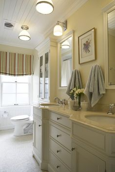 Refined Cottage Bathroom    A country-style striped blind offers cottage charm.      The beadboard ceiling, chair rail and reproduction antique leaded glass cabinets all contribute to the casual-yet-polished feel of this family bathroom.