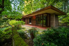 """10/9/2012--Sammamish, WA, USA..VIEW: Exterior showing rear of house with bedrooms on small, paved veranda...Architect Frank Lloyd Wright planned his """"Usonian"""" homes to be affordable for middle-class families. The 1,9500 square foot Brandes home is for sale in Sammamish, Washington (30 minutes from Seattle) at $1.39 million. It features three bedrooms, two bathrooms and a small, separate office/study space...The home was built in 1952, and has redwood trim and Wright's original furniture and…"""