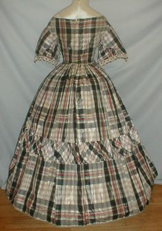 1860's Plaid Silk Ballgown Dress | eBay Fabric has a white, black, red and light mauve plaid pattern.  Bodice has short flared cap style sleeves decorated with white and black silk trim.  Trim has attached silk balls.  Front of the bodice is trimmed with gold silk balls.  Neck, armscyes and waist are piped.  Bodice lined wt cotton & has back hook and eye closure.  Skirt fully lined wt cotton & attached to the waist wt cartridge pleating. Bust 31 Waist 24 Skirt length 37 Width at hemline 140.