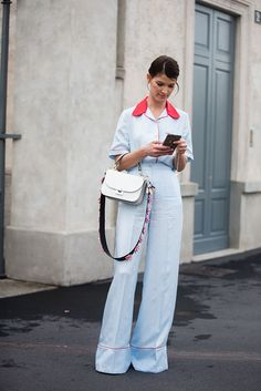 Hanneli Mustaparta  ブロガーのハネリが着たパジャマ風セットアップはプラダのもの。爽やかなペールブルーに、赤いパイピングと襟がアクセントになっている。シャツをしっかりウエストインすることで、スタイリッシュに着こなした。ストラップがアクセントになったバッグも、ウェアと同じくプラダのもの。