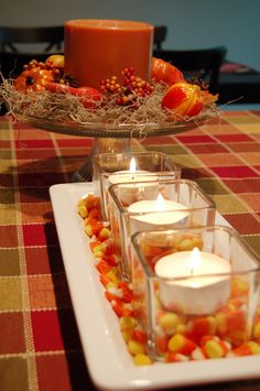 Pour candy corn around votive candles for a cute fall table display.