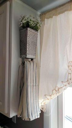 Cute Idea! Metal cheese grater turned upside down as a towel holder. Flowers decorate the top!
