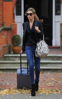Abbey Clancy in Frame Denim skinny jeans, black shirt, and black Stella McCartney blazer worn with Tom Ford sunglasses, black ankle boots, and Alaïa animal-print bag.