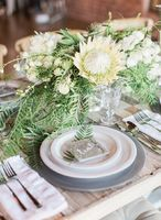 The exposed brick and wood beams at the Howl Event Space in Long Beach, CA were the backdrop for this next stunning editorial. Danielle Mitchell Events and Brian LaBrada Photography teamed to bring this nature inspired shoot together using organic elements of  wood, slate and some of prettiest proteas we've seen!Photographers: Brian LaBrada PhotographyCoordinators & Stylists: Danielle Mitchell EventsVenues & Officiants: Howl Event SpacePaper Goods & Calligraphy: Ink Paper and JoyFlowe...