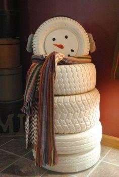 des pneus blanchies, empilées et déguisées en bonhomme de neige original
