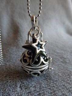 Bola de grossesse avec motif d'arabesques, contenant une bille noire, avec une étoile noire et argentée, en sautoir : Maman par bola-de-grossesse