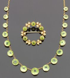 Victorian 15ct gold mounted green peridot and seed pearl circular brooch set with six green peridots interspersed by seed pearls in a shamrock setting, 1.25in diameter, and an Edwardian gold coloured metal necklace set with seventeen circular graduated peridots, 17.5ins
