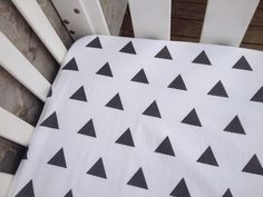 Image of White with black triangle fitted cot sheet.