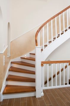 Closed cheek staircase in Merbau wood with a curved spiral, white cheeks and railings, energy-saving LED lighting embedded in the wall cheek. Closed cheek staircase in Merbau wood with a curling in the spiral, white .