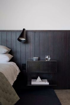 Charming bedroom with a rustic touch and boarded wall. The modern wall lamp provides a mid-century touch to the whole setting.