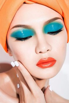 Bright glossy eyes with an orange lip.