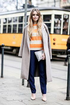 Street style look com blusa listrada laranja e calça alfaiataria, clutch metalizada e sobretudo bege.