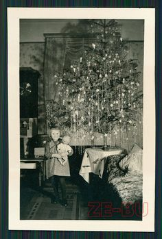 Vintage Christmas Day Photo of a girl with a doll found under the Christmas tree. c1938