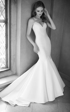 Strapless fit-and-flare wedding dress featuring an ultra-low strapless sweetheart neckline, structured bodice, a dramatic skirt and traditional train.