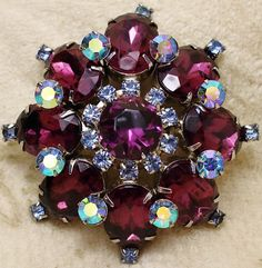 """Vintage Unsigned Beauty Amethyst Purple AB Rhinestone Domed Brooch Pin is a fabulous floral domed brooch with a large round amethyst glass """"stone"""" at its center encircled by small blue AB coated chato"""