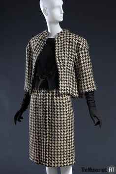 Courreges charcoal and white houndstooth wool suede suit, 1961 France.  Infused with a fashion-forward sensibility, the suit reflects the couturier's training at Balenciaga. Courrèges reinforced the suit's angularity with a bold houndstooth fabric, the pattern matched with precision. Advanced tailoring techniques were required for the jacket to stand away from the body in such a sculptural manner. Museum at FIT New York.
