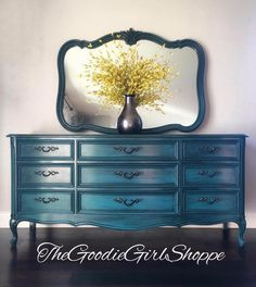 """This piece was finished completely with General Finishes products and I couldn't be more thrilled with the results! The dresser was painted using a custom blend of Milk Paints in Patina Green, Emerald, Coastal Blue and Corinth Blue, which created a wonderful peacock blue. The entire body was then glazed using Glaze Effects in Pitch Black. The coordinating mirror received the same paint and glaze treatment. The top of the dresser was stripped and stained using Java Gel Stain. Everything was…"