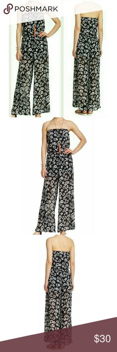 """Black Sleeveless Jumpsuit with Daisy NWT M Gorgeous black jumpsuit with white daisies. Sleeveless. Bodice with elastic to hold up. 100% polyester.  Size is Junior Medium.    Measurements:  52 inches Total Length  28 inches Bust Around  26 inches Waist  36 inches Hip Around  inseam: 33""""inches Want & Need Pants Jumpsuits & Rompers"""
