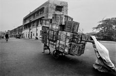 Wife and husband pushing a cart. Delhi India. 1979. © Raghu Rai / Magnum Photos