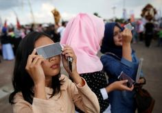 People test filters for watching a solar eclipse near the Ampera Bridge on the Musi River the day before thousands of people are expected to gather to witness the event in Palembang, South Sumatra province, Indonesia March 8, 2016. REUTERS/Darren Whiteside