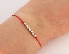 Bracelet Kabbale / le fil rouge / Red string Kabbalah Bracelet / the red string avec 7 perles représentatives des 7 jours de la semaine en argent massif 925. Les perles sont montés sur du nylon qui peut être mouillé. Taille femme environ 16 cm / Taille Homme environ 17/18 cm Pour une