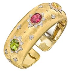 Buccellati 18k Gold & Multicolored Gemstone Cuff Bracelet – Wide multicolored gemstone cuff bracelet, accented by three oval-shaped gemstones, including a rubellite in the center flanked by a yellow sapphire and green tourmaline to the sides, the three gemstones set within a chased starburst pattern in white gold, the cuff mounted in textured 18k yellow gold, with a hinge on one side, numbered 20460, signed Buccellati Italy.