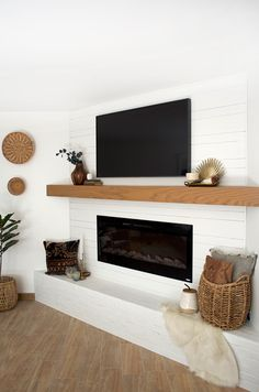 White shiplap on a fireplace makeover I'm finally sharing all the details on our Simple and Modern Mantle Makeover with alternating sized shiplap and white brick! Basement Fireplace, Shiplap Fireplace, Home Fireplace, Fireplace Remodel, Living Room With Fireplace, Fireplace Design, Fireplace Ideas, Corner Electric Fireplace, Wall Mounted Fireplace