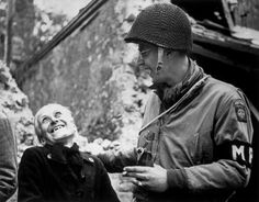 An American paratrooper and an old French woman enjoy a joke together in the shell-torn streets of Sainte Mere Eglise, 20th June 1944. (Keystone / Getty Images)