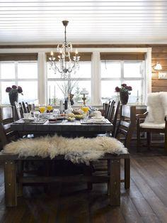 BEVISSTE VALG: Hytteeierne hadde bestemt seg for å kjøpe lysekrone før hytta var ferdig. Benken foran spisebordet har de laget selv. Alle stolene er ikke like, noe som var et bevisst valg. De ønsket få frem kontraster i interiøret. Stolene har de trukket om selv og det gamle bordet er beiset.