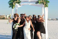 Bride and bridesmaids with fun masks on Siesta Key Beach, Florida