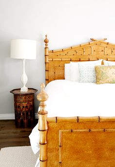 Bedroom with white walls, dark wood floors, white bedding, wooden bed frame, and colorful patterned pillows
