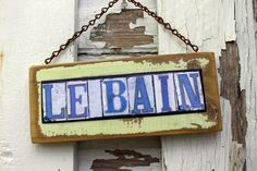 "Le Bain Bathroom Door Sign. New Orleans Street Tile Sign reading ""Le Bain"" French for ""The Bath"". Sign measures approximately 3 - 3"" tall x 8"" wide. Le Bain signs are made from salvage wood and photographic images designed after the old street corner tiles of New Orleans. Images from original street name tiles are used to create wording for this and many other sayings. Lettering is finished with various coats of acrylic, and old salvage chain or wire for hanging."