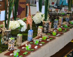 Juice boxes wrapped in jungle theme scrapbook paper & tied with raffia... could do this for candles to give as party favors.