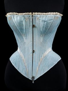1864 Corset (front) - Victoria and Albert Museum at http://collections.vam.ac.uk/item/O15546/corset-unknown/    Silk, edged with machine-made lace, reinforced with whalebone and metal eyelets, cotton twill lining. The corset was worn over the chemise and it moulded the figure of the wearer into the fashionable shape of the day. It did not need to be very tightly laced, for the illusion of a small waist was created by the very wide circumference of the crinoline.