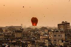 People gathered on terraces or rooftops of their houses everyone releases paper lanterns after sunset and the sky covered with tiny colourful floating lights for the festival of Makar Sankranti or Uttarayan in the old Khadia area of Ahmedabad in Gujarat, India