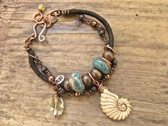 ♥ 10% of animal or sea creature amulet designs donated to animal rescue and rehab ♥ Handmade copper double strand bohemian bracelet... beach chic jewelry from Rio Jewelry Studio. Hand carved ox bone nautilus shell amulet on 3mm genuine cord with aqua ceramic beads, copper trade beads and a gorgeous copper wire work citrine nugget. #rio jewelry studio