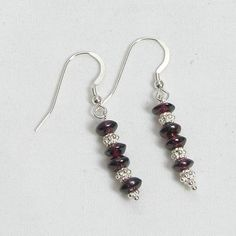 Handmade garnet earrings feature semi-precious red garnet rondelle gemstones, fishhook-style earwires, and sterling silver accents, product sku E0135.
