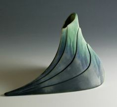 Folded Leaf Vase by Newman Ceramic Works. Alan & Brenda Newman have been full time potters working from their home studio since 1978. They are known for their functional porcelain which combines botanic elements with sculptural forms. Their original matt microcrystalline glazes make each piece beautifully unique. This award winning work is shown in galleries and museum shops throughout the country.