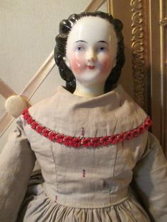 Antique RARE China Head Doll Mary Todd Lincoln with Snood 18 inch Circa 1860 | eBay Rare very early circa 1860's Mary Todd Lincoln china head shoulder-plate Measures almost 18 inches  Original multi-layered cotton clothing is still in lovely condition along with her red oil cloth boots. Shoulder plate has been repaired in a few areas as shown. Dress is completely sewn onto doll and will not be removed. Rare long haired, high brow curls has snood that does show paint wear to edges.