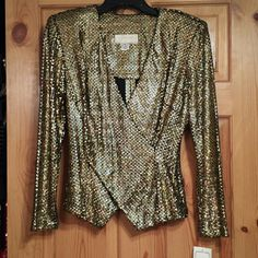 """HPNWT Gorgeous Golden Blazer ~~Janine of London golden, shiny blazer ~~pull over style ~~party style! It fits me a touch tight @ 34C Some stretch.  ~~Bust 17"""" flat, Length 23"""" sides 25"""" at from criss cross ~~beautiful material from Italy & reflective of colors      around ~~Hand wash cold (no twisting), dry flat.  ~~Tag says small but will fit medium see the measurements.Hi Deplace, My many thanks to: @adri_nyc_closet selected """"NWT Italian fabric, Gorgeous Golden Blazer"""" as a host pick for…"""