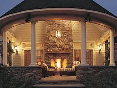 Classic lines, primeval appeal. Part of a farmhouse renovation, this stone porch begs to be enjoyed. Classic columns, traditional trim details, and a symmetrical layout contrast nicely with the rustic look of the stone fireplace, kneewalls, and floor.