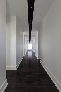 deep wood floors + clean white walls + simple modern baseboards and a central lign of light  via tumblr: takeovertime