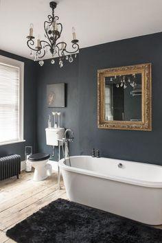 huge bathroom bath tub, black walls, chandelier, and gold mirror